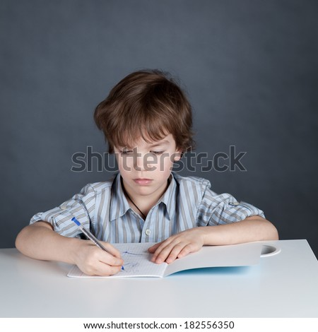Thinking  schoolchild sitting at desk and writing in a notebook pen, portrait on gray background, studio, training