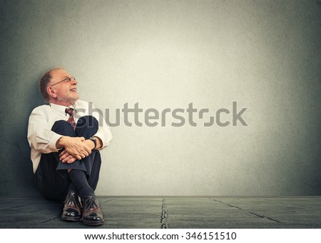 Thinking senior man sitting on floor isolated on gray wall  background. Mature male model corporate executive  smiling looking up dreaming  - stock photo