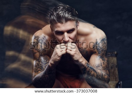 Thinking shirtless muscular man with tattooes on his body.