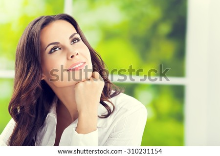 thinking smiling attractive brunette businesswoman looking up, at office - stock photo
