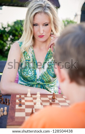 Thinking Woman playing Chess with her Son - stock photo