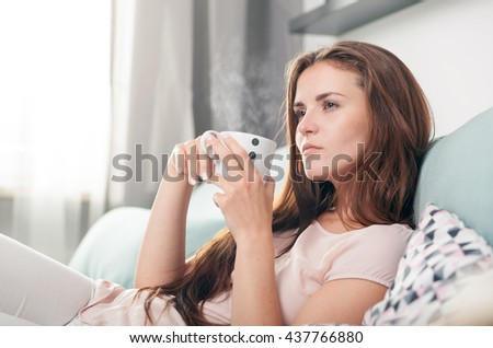 Thinking woman sitting on couch at home and drinking coffee, casual style indoor shoot - stock photo