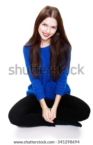 Thinking woman sitting on floor isolated on white background. Beautiful young mixed race Caucasian / Asian female model smiling looking up.
