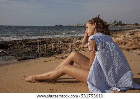 Thinking woman sitting on the beach wearing shirt only