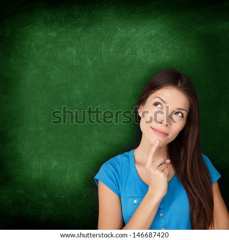 Thinking woman student or teacher with blackboard standing contemplative and pensive looking up to the side at empty green chalkboard copy space for your text or design. Multiracial Asian Caucasian. - stock photo