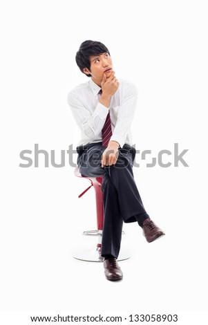 Thinking Young Asian business man sitting on the chair isolated on white background.