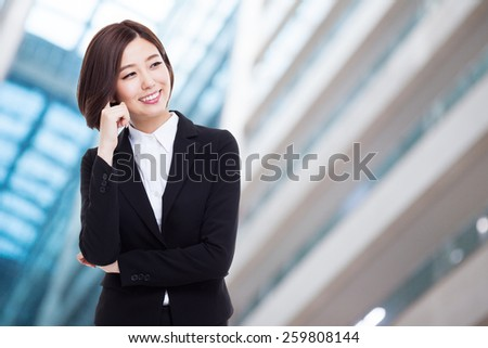 Thinking young Asian woman isolated on business background - stock photo