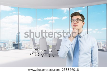 thinking young businessman standing in modern office - stock photo