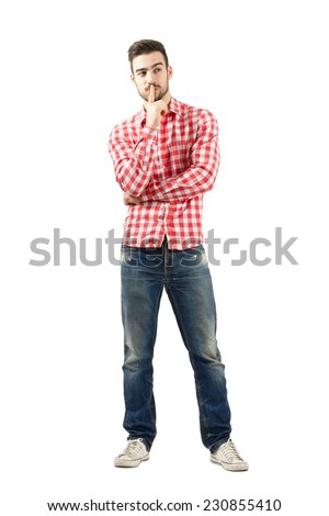 Thinking young guy with finger over his mouth. Full body length portrait isolated over white background.  - stock photo