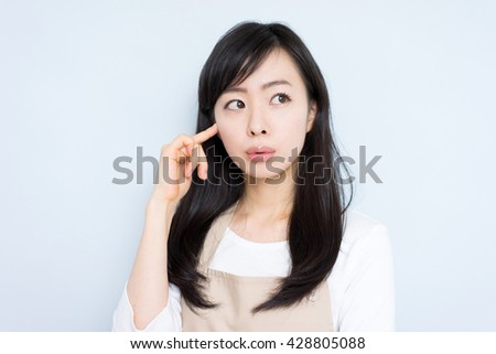 thinking young housewife with apron against blue background - stock photo
