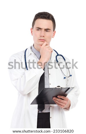 Thinking young male doctor holding a clipboard. Three quarter length studio shot isolated on white.