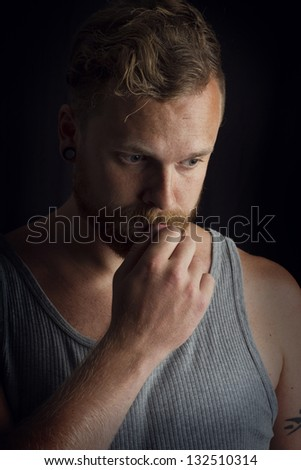Thinking young man / rocker with tattoos and ear rings.