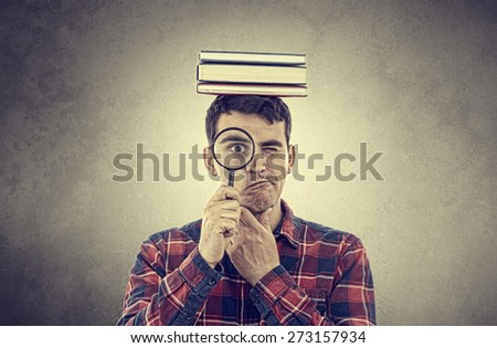 Thinking Young man student holding magnifying glass and a  stack of books on head isolated over grey background.Curious young student man holding books with a magnifying glass. - stock photo