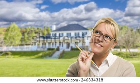 Thinking Young Woman With Pencil in Front of Beautiful House. - stock photo