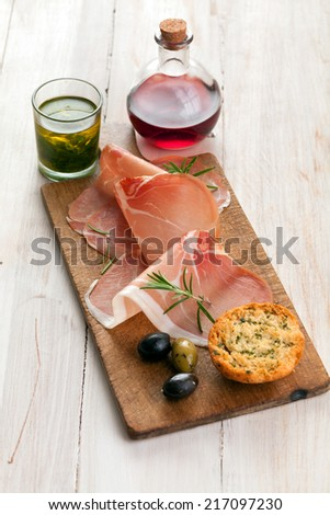 Thinly sliced gourmet Italian prosciutto ham with cured olives and golden toasted herb bread on a wooden board on a rustic white table - stock photo