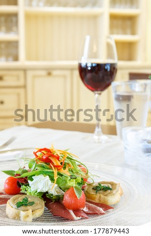 Thinly sliced Prosciutto or Parma ham served topped with fresh salad on a table set with red wine and iced water