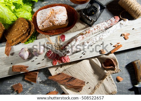 thinly sliced salami ,bread , garlic ,black pepper , lettuce on a wooden texture on the background of the living flame in the kerosene lamp