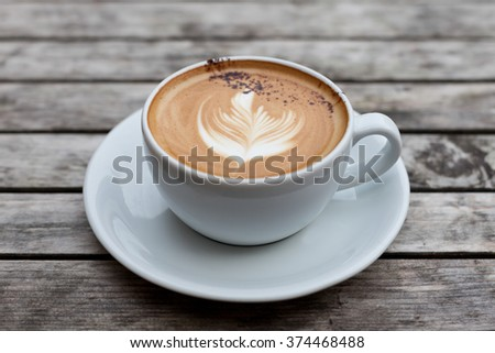 Third wave coffee latte art cappuccino with natural light on reclaimed wood - stock photo