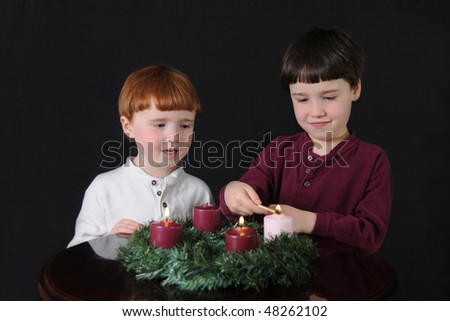 Third Week of Advent: Two brothers light an Advent wreath to prepare for Christmas - stock photo