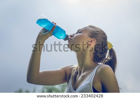 thirsty athlete drinking power drink after long run - stock photo