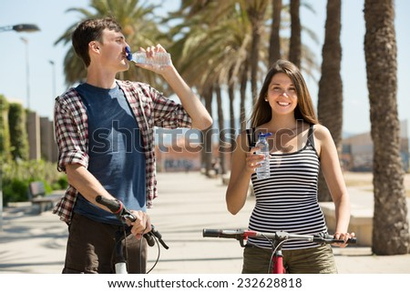 Thirsty couple on bicycles taking a refreshing drink of water from bottle - stock photo