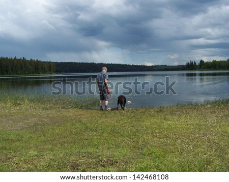 Thirsty dog at the lake with master - stock photo