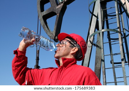 Thirsty Oil Industry Worker.Thirsty oil worker drinking water from bottle in front of the pump jack.