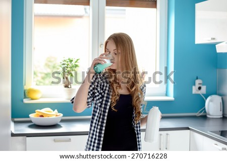 Thirsty young blond woman drinking milk from a glass in the kitchen. Holding the bottle in the other hand - stock photo