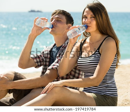 Thirsty young couple enjoying a refreshing drink of water from bottle outdoor - stock photo