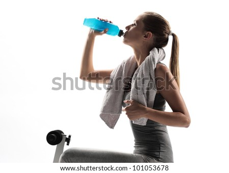 Thirsty young woman drinking after fitness workout. white background