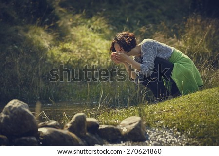 Thirsty young woman drinking fresh water with her hands from a mountain creek on a sunny summer day. - stock photo