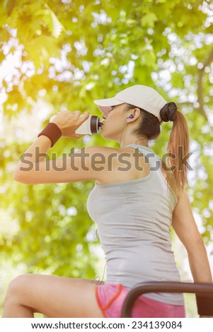Thirsty young woman drinking water and listening to the music while resting. - stock photo