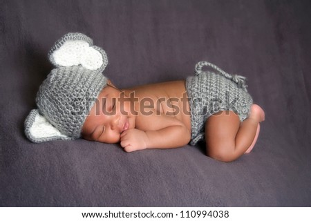 Thirteen day old smiling newborn baby boy wearing a gray crocheted elephant hat and diaper cover. He is sleeping on his stomach on gray fleece fabric. - stock photo