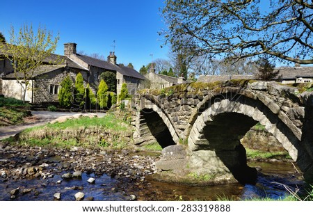 Thirteenth century packhorse bridge and the village of Wycoller. - stock photo