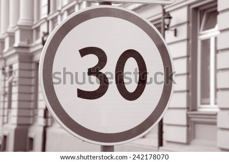Thirty Kilometer Per Hour Speed Limit Sign in Urban Setting in Black and White Sepia Tone - stock photo