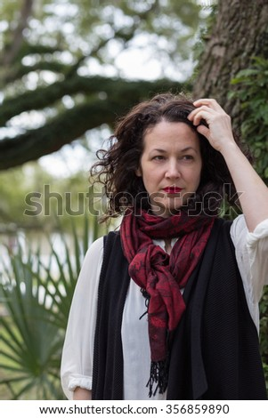 Thirty-something thoughtful woman looking into the distance in a park - stock photo