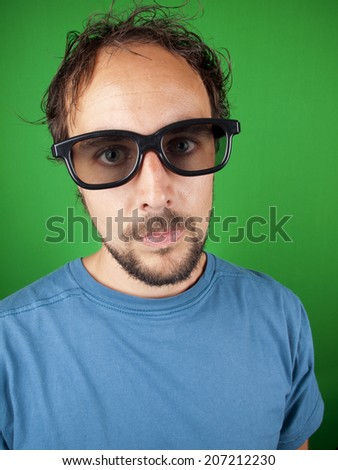 Thirty year old man with 3d glasses is watching a boring movie over a green background - stock photo