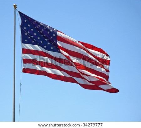 This American flag is flying it's red, white and blue symbol against a bright blue sky.