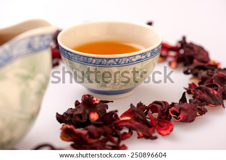 This brew smells lovely. Image of teapot and a cup of tea surrounded by flower tea composition isolated on white background with selective focus - stock photo
