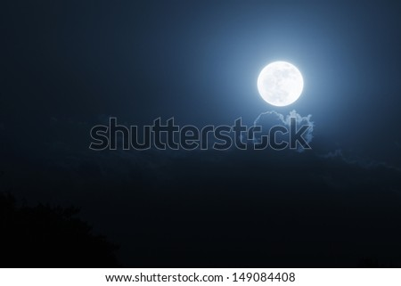 This bright, shining moonrise seems to have popped through the clouds as it illuminates the night time sky with the brilliance of the sun. - stock photo