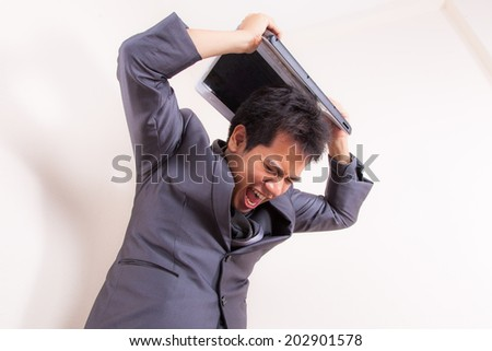 This businessman has lost his temper completely as he stand with his laptop angry and frustrated. Things are not going his way! - stock photo