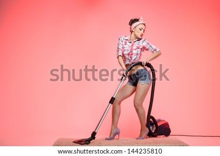 This carpet is so dirty! Sexy young housewife cleaning the carpet with vacuum cleaner and dancing - stock photo