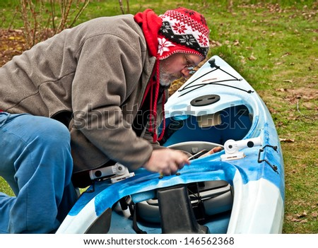 This Caucasian, middle age man is working on a kayak in the yard during off season.  He's wearing a hat and kneeling beside the canoe with tools. - stock photo