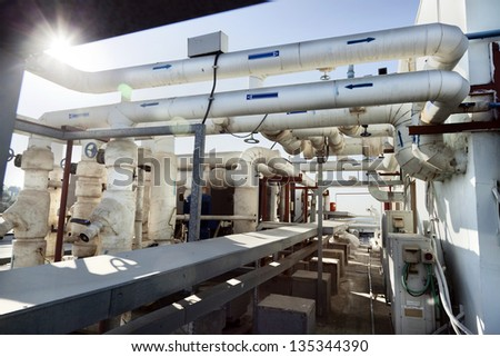 This complex pipes & valves system is located on the roof of an office building, and is part of the water supply system of the HVAC commercial air-conditioning of the building. - stock photo