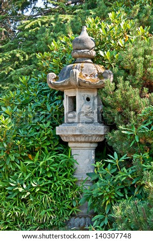 This concrete pole is a Japanese style decor in a garden setting with plants and various evergreen trees.  Peaceful and quiet place. - stock photo