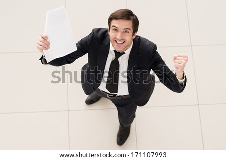 This contract is mine! Top view of excited young man in formalwear holding a paper in one hand and gesturing
