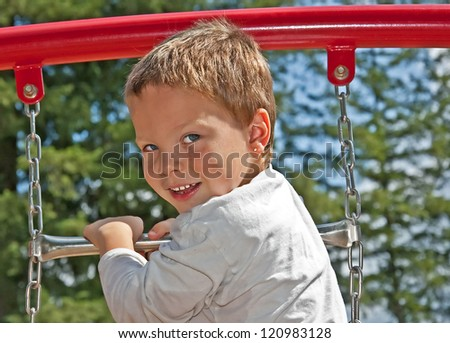 This cute 4 year old Caucasian boy with blue eyes and freckles in playing on some playground equipment outdoors.  He's wearing a long sleeve white t-shirt. - stock photo