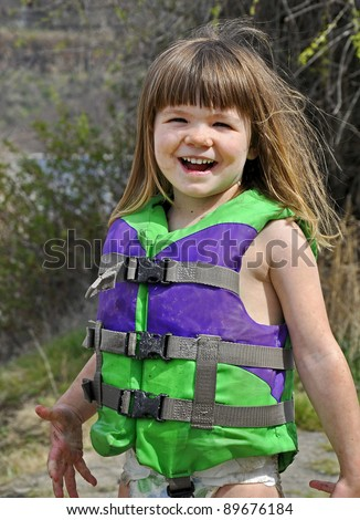 This cute 3 year old Caucasian girl is smiling and happy while playing outdoors.  She's wearing a green life vest and covered in mud as she's been playing. - stock photo
