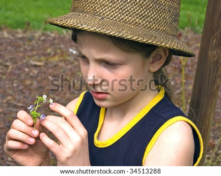 This cute 8 year old Caucasian girl is wearing a natural hat and closely studying a small flower. - stock photo