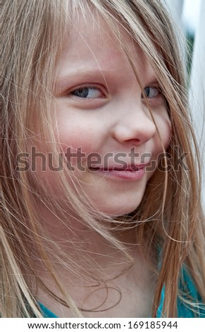 This cute 5 year old girl portrait is a closeup of her face.  She is a Caucasian with long blond hair and from a side view.  Model is smiling sweetly. - stock photo